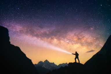 Silhouette of the man standing against the Milky Way in the mountains with a flashlight in his hands. Nepal, Everest region, view of the mount Thamserku (6,608 m) from Thame village (3,750 m).